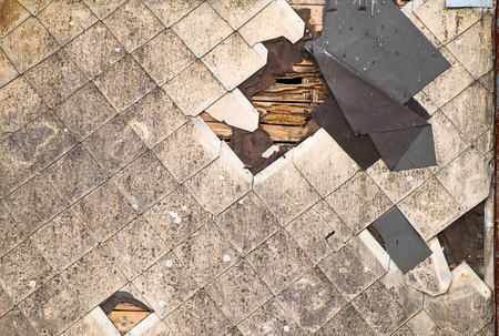 Foto de Old damaged roof of asbestos shingles requiring repair. Dirty beams and torn waterproofing of roofing material. - Imagen libre de derechos