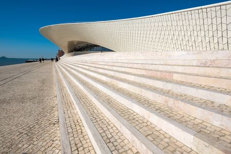 Foto per LISBON, PORTUGAL - FEBRUARY 12, 2019: People walk near famous MAAT Museum in Lisbon near river Tagus and Landmark 25 of April bridge. - Immagine Royalty Free