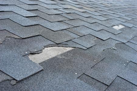 Photo pour Ð¡lose up view of asphalt shingles roof damage that needs repair. - image libre de droit