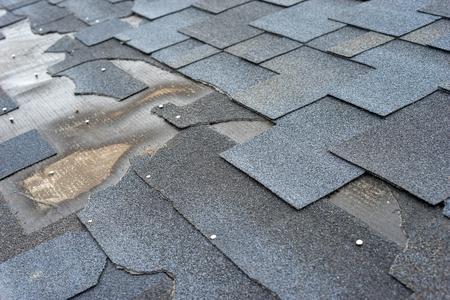 Photo pour Ð¡lose up view of bitumen shingles roof damage that needs repair. - image libre de droit