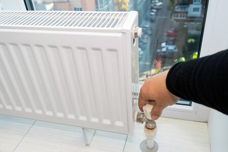 Photo pour Hand adjusting the knob of heating radiator at home a cold season. - image libre de droit