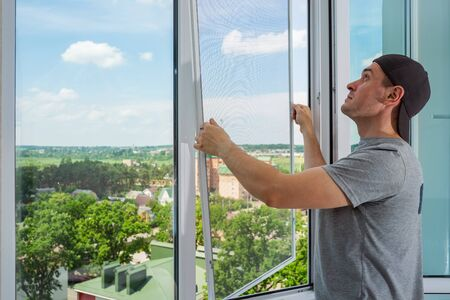 Photo pour A contractor worker installing mosquito wire screen on house plastic windows to protect from insects. - image libre de droit