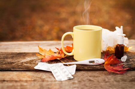 Cup with hot tea and thermometer showing high temperature along with pills and nose drops on wooden surface, flu season in autumn