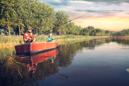 Foto de father and son with fishing rods  fishing in a wooden boat against background of beautiful nature river - Imagen libre de derechos