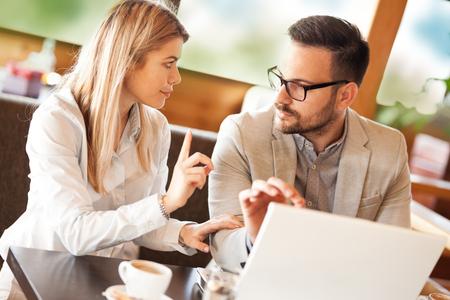 Photo pour businessman using a laptop to discuss information with colleague in a modern cafe - image libre de droit