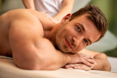 Foto de Young  man receiving back massage in beauty and spa center. - Imagen libre de derechos