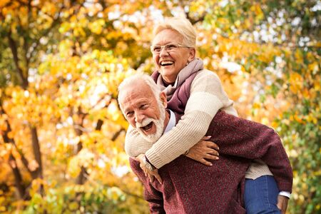Foto per Senior couple laughing and having fun in autumn park. After all these years as at the first meeting - Immagine Royalty Free