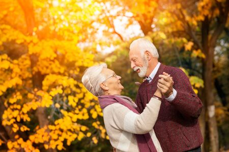 Old senior couple dancing happy together in nature. Romantic autumn day