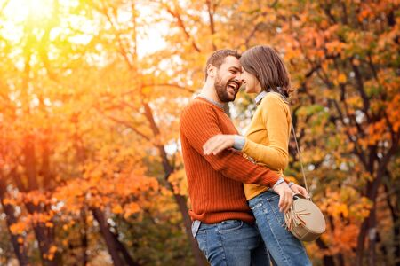 Photo pour Young couple in love outdoor in autumn park. Couple hugging. Young beautiful couple in love staying and kissing on the autumn park on sunset. Soft sunny colors - image libre de droit