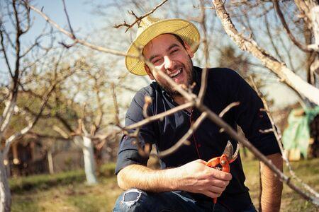 Foto für Smiling farmer pruning branches of fruit tree in season of the spring. - Lizenzfreies Bild