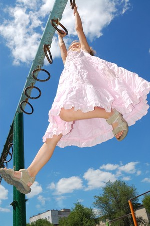 Photo pour  5 year old girl hanging on gymnastic rings at a storts ground - image libre de droit