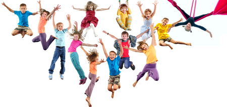 Foto de Large group of happy cheerful sportive children jumping, sporting and dancing. Isolated over white background. Childhood, freedom, happiness, active lifestyle concept. - Imagen libre de derechos