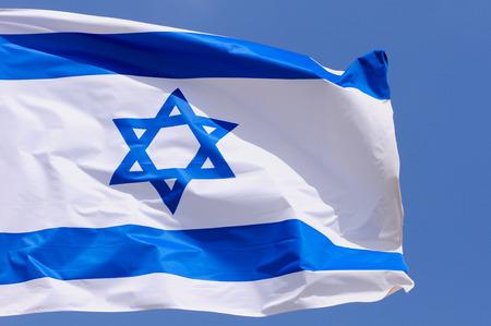 big flag of Israel over blue sky