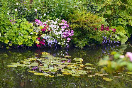 Foto de Beautiful Claude Monet's Garden of Giverny, Normandy, France in auturmn with the iconic green Japanese bridge reflecting in the water lilies pond - Imagen libre de derechos