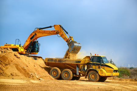 Photo pour Earthmover loads the ground in the truck at the road construction - image libre de droit