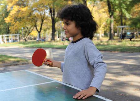 Cute little boy play table tennis in the park