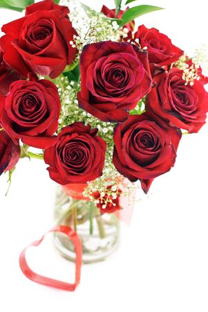 A bouquet of deep red roses in a vase with red heart shape, shallow depth of field with selective focus
