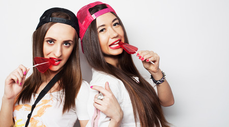 Fashion portrait of two young pretty hipster girls wearing bright make up and holding candys. Studio portrait of two cheerful best friends sisters having fun and making funny faces.