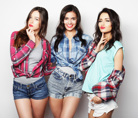 Three best friends posing in studio, wearing summer style outfit and jeans shorts. Girls smiling and having fun.の写真素材