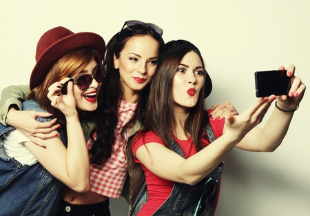 Photo pour Three stylish sexy hipster girls best friends taking selfie with mobile phone - image libre de droit