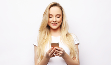 Young blond woman  with long hair holds modern smart phone, reci