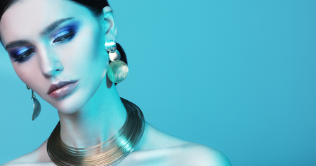 Foto de beautiful fashion model wearing elegant jewelry in color light - Imagen libre de derechos