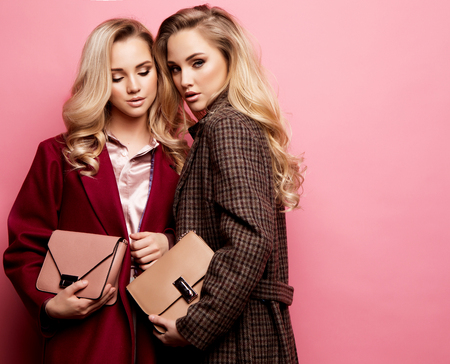 Foto de Two sweet young women posing in nice clothes, coat, handbag. Sisters, twins. Spring fashion photo. - Imagen libre de derechos