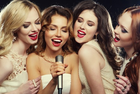 Photo pour lifestyle, party and people concept - four beautiful stylish girls singing karaoke at the club - image libre de droit