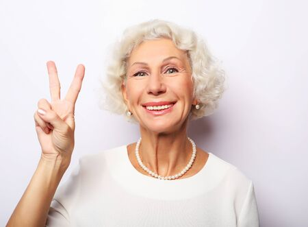 Photo pour Old woman laugh and showing peace or victory signat camera. Emotion and feelings. Portrait of expressive grandmother. - image libre de droit