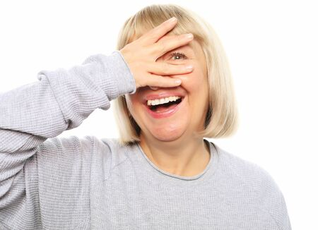 Photo pour Funny old lady closes her eyes with her hand, peeps and laughs, isolated on white - image libre de droit