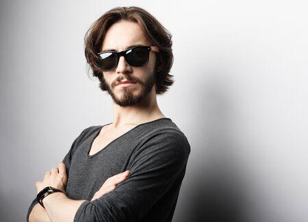 Photo pour Fashion and people concept: portrait of a young man wearing sunglasses on light grey background - image libre de droit