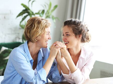 Photo pour Beautiful senior mom and her adult daughter are hugging, looking at camera and smiling. At Home. - image libre de droit