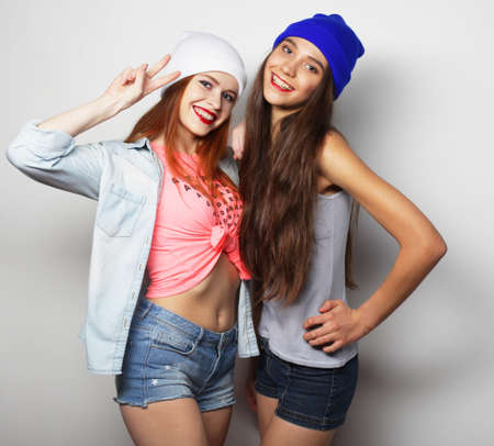 Photo pour Cute teen girls smiling at camera and making a V sign, adolescence and friendship concept - image libre de droit