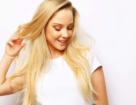 Photo for lifestyle and people concept - Beautiful happy blond girl touches her hair. Casual clothes. White background. - Royalty Free Image