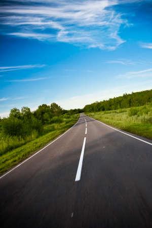 black highway road under blue skies