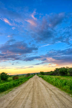 Photo for dirt road to sunset through the fields - Royalty Free Image