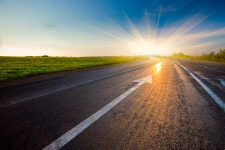 black asphalt road with arrow to sunset