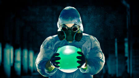 man in protective costume and respirator holding danger ball