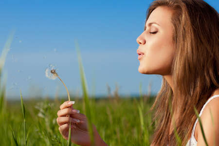 beautiful woman blowing to dandelio on green field