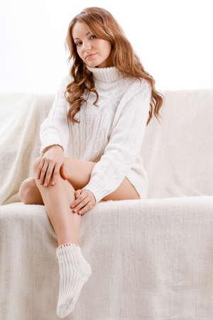beautiful sexy woman wearing sweater sitting on the sofa