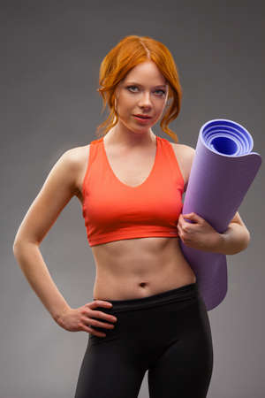 red -haired woman holding fitness mat