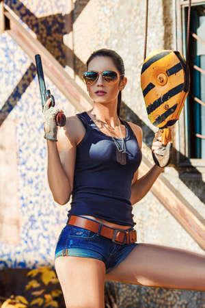 sexy brutal woman wearing sunglasses holding handgun