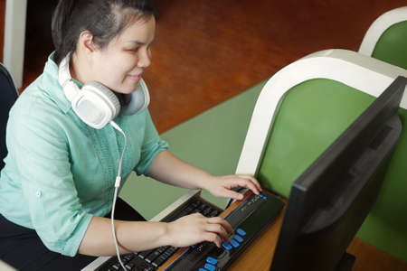 Foto de Asian young blind woman with headphone using computer with refreshable braille display or braille terminal a technology device for persons with visual disabilities. - Imagen libre de derechos