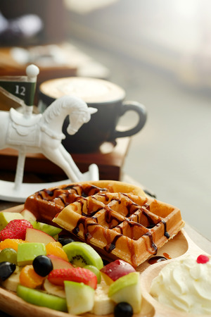 Waffle pour chocolate sauce and fruit mixed Served whipping cream and drink with Hot cappuchino for appetizer