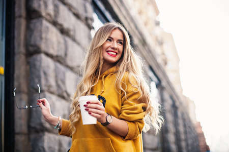 Foto per Stylish happy young woman wearing boyfrend jeans, white sneakers bright yellow sweetshot.She holds coffee to go. portrait of smiling girl in sunglasses Street fashion concept - Immagine Royalty Free