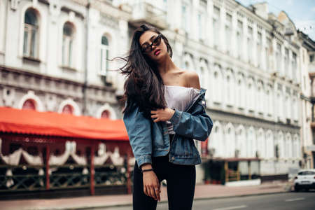 The concept of street fashion. Young beautiful model in the city. Dynamically young girl walks down the street.Hair fluttering in the wind