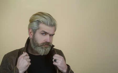 Foto de Fashion handsome man, serious male model portrait wear leather jacket, young guy over gray background. - Imagen libre de derechos