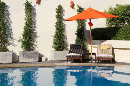 Lounge chairs with umbrella in a swimming pool invite you to relax