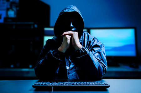 Photo pour Anonymous computer hacker in white mask and hoodie. Obscured dark face with keyboard computer in the dark. Data thief, internet attack, darknet and cyber security concept. - image libre de droit