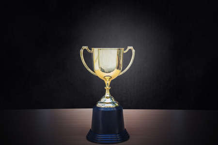 Photo for Golden trophy placed on top of old wooden table in front of dark background copy space ready for your design win concept. - Royalty Free Image